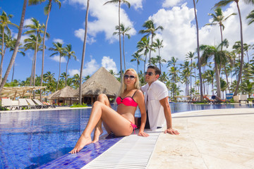 young man and woman - relax near the swimming pool