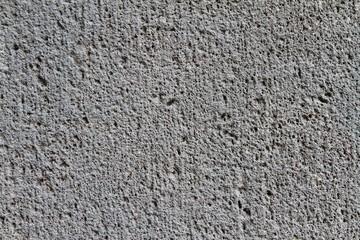 Nahaufnahme einer groben, dunkelgrauen Betonwand
