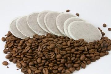 Kaffeepads einem Haufen aus Kaffeebohnen