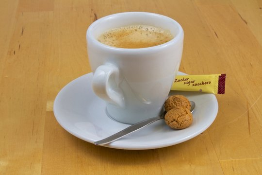Kaffeetasse mit Zuckertütchen und Gebäck