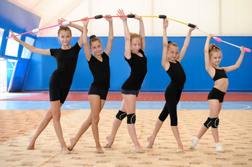 Young female gymnasts making bow with Indian clubs