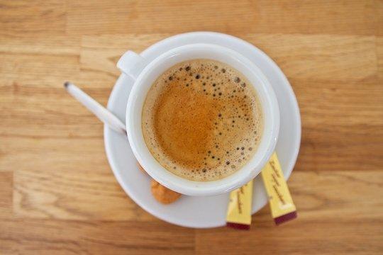 Kaffeetasse mit Zuckertütchen und Gebäck auf brauner Tischplatte