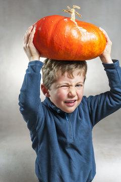 Little boy making a face with heavy orange pumpkin hat