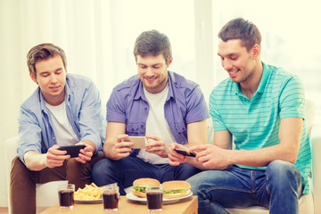 smiling friends taking picture of food at home