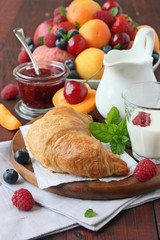 Breakfast with fresh croissant , milk, raspberry  and fruits.