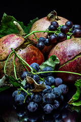 Pomegranate and wild grapes on a black background