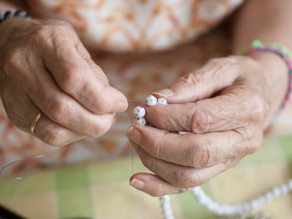 Hands of elderly woman threading a necklace