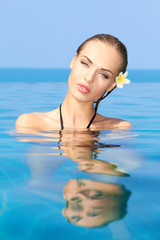 Sensual Woman in Blue Water with Flower on Ear