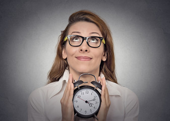 Portrait woman with alarm clock on grey wall background
