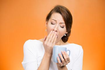 sleepy yawning woman holding cup of coffee on orange background