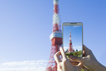 Hand to be photographed on a mobile phone the Tokyo Tower