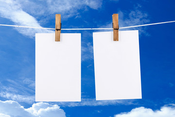 Paper hanging in blue sky  background