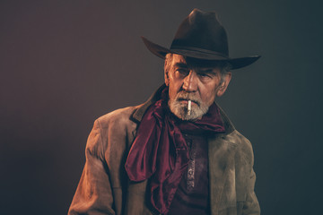 Old rough western cowboy with gray beard and brown hat smoking a Wall mural