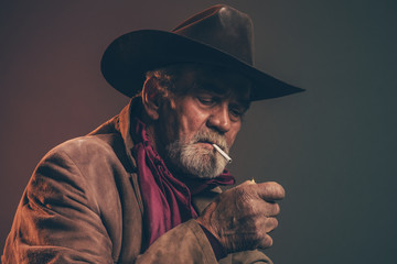 Old rough western cowboy with gray beard and brown hat lighting Wall mural