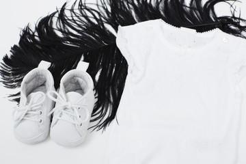 Booties, babygro and black feather, studio