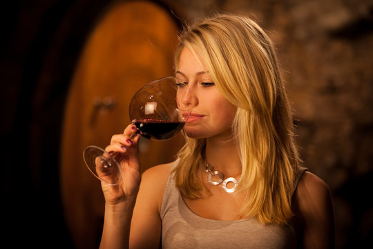 Beautiful young blond woman tasting red wine in a wine cellar