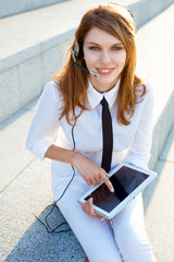 Contact center girl with hands free headset holding PC tablet