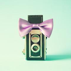 Vintage photo camera with purple bowtie