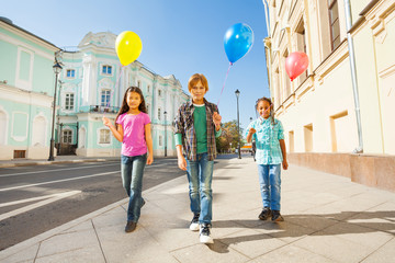 Three multinational kids with colorful balloons