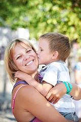 Little boy kisses his happy mother