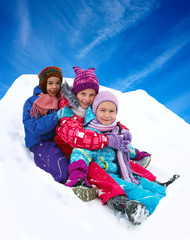 Winter fun, snow, happy children sledding at winter time