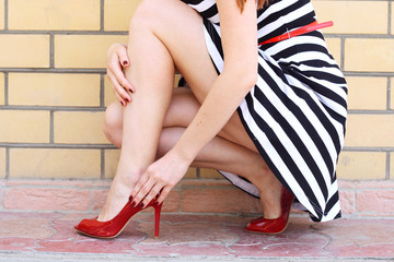 girl legs in red high heel shoes and short skirt outdoor