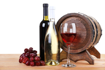 Wine in goblet and in bottles, grapes and barrel