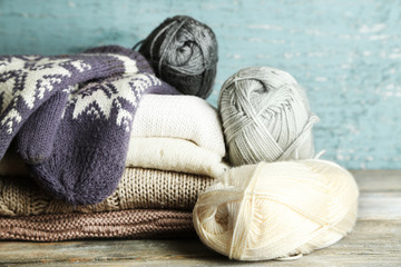 Knitting clothes, yarn and mittens, on wooden background