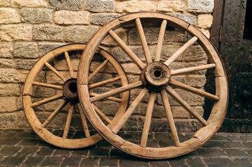 rustic wagon wheels in front the wall old city Baku Azerbaijan