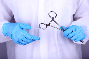 Surgeon's hands holding clip closeup