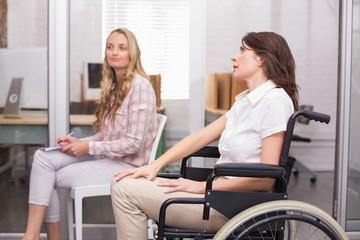 Businesswoman in wheelchair listening to presentation