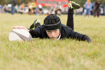 Young boy on the ground with a rugby ball