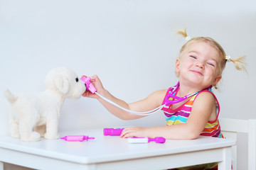 Little girl playing doctor with puppy toy
