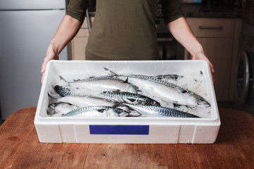 Woman with box of mackerel
