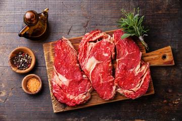 Raw fresh meat Ribeye steak entrecote and seasoning on dark wood
