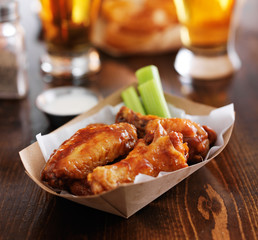 hot bbq buffalo chicken wings with ranch sauce and celery