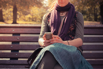 Young woman on park bench using her phone