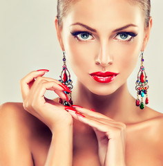 Girl with red nails and fashion earrings