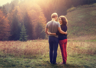Two inlove young people on the sunset forest glade