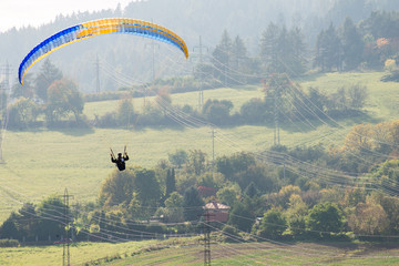 Paraglider over high voltage pylons and lines