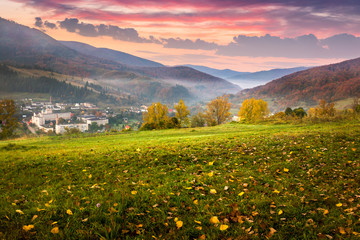 village on hillside meadow with foliage in mountain at sunrise