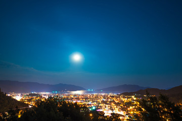 clear sky and full moon over night city