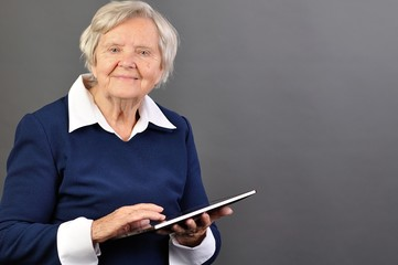 Senior happy woman with tablet against grey background.