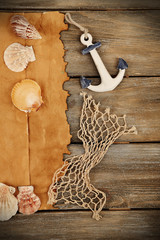 Decor of seashells, starfish and old paper on wooden background