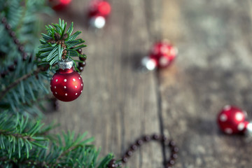 Red ball on fir of christmas tree over rustic wooden background.