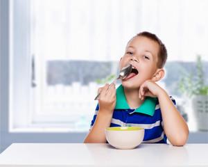 Little boy eating a healthy breakfast in the kitchen