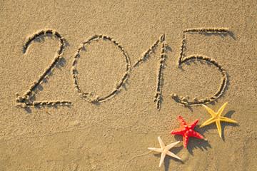 2015 written on sandy beach