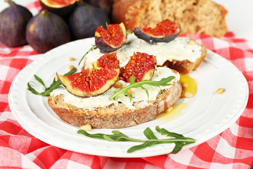 Tasty sandwiches with sweet figs and cottage cheese on plate