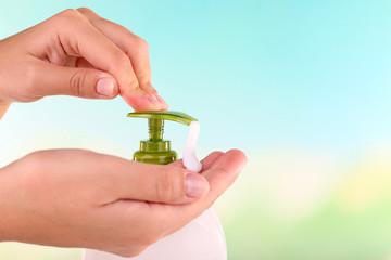 Female hands using liquid soap on light background