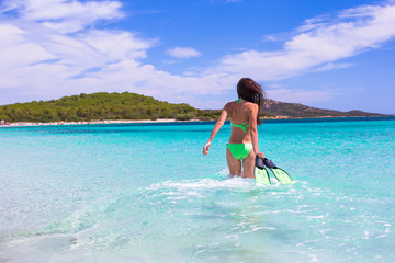 Young woman with snorkeling gear on tropical beach